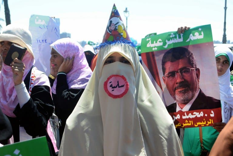 A supporter of Egypt's deposed president Mohamed Morsi, wearing a pin which reads in Arabic