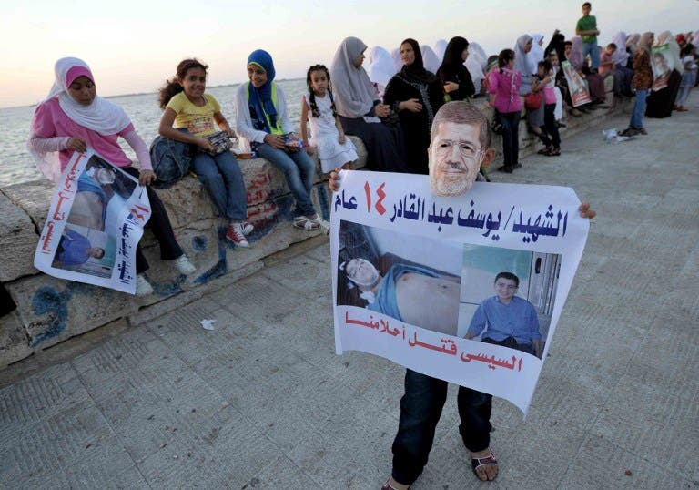 A supporter wears a mask of Egypt's deposed president Mohamed Morsi showing a portrait of a child, victim of the clashes during a protest in the Mediterranean city of Alexandria on August 6, 2013. (AFP)