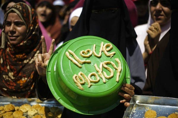 An Egyptian woman displays a pro-Morsi slogan made of pastry to be used for Eid al-Fitr cookies as supporters of ousted president Mohammed Morsi take part in a sit-in outside Cairo's Rabaa al-Adawiya mosque on August 7 (AFP)
