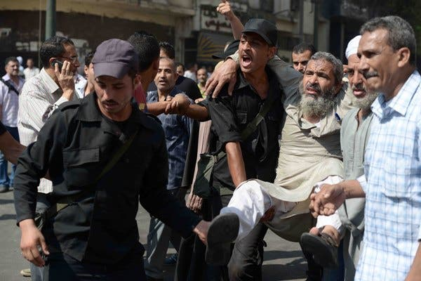 Egyptian policemen carry an Islamist man outside Cairo's Al-Fath mosque where Islamist supporters of ousted president Mohamed Morsi held up on August 17, 2013. (AFP)