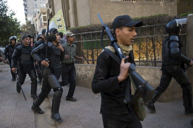 Egyptian riot policemen run after Muslim brotherhood members following a demonstration in Cairo's eastern Nasr City district on December 27, 2013. [AFP]