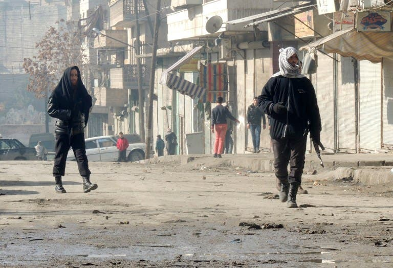 Rebel fighters, one holding a weapon, walk in a street on January 7, 2014 in the northern Syrian city of Aleppo. [AFP]