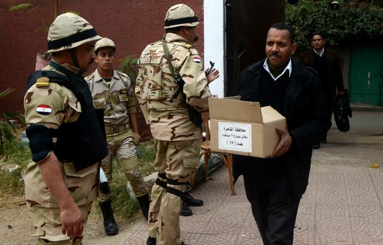 A man carries a box full of voting ballots near Egyptian soldiers standing guard outside a school that will be used as a polling station on January 13, 2014 in Cairo. [AFP]