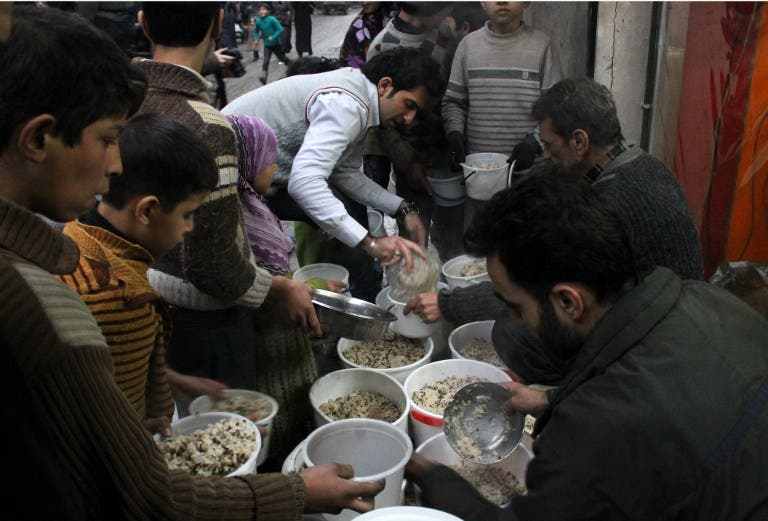Syrian youths gather to receive aid food in the northern Syrian city of Aleppo on January 14, 2014. [AFP]