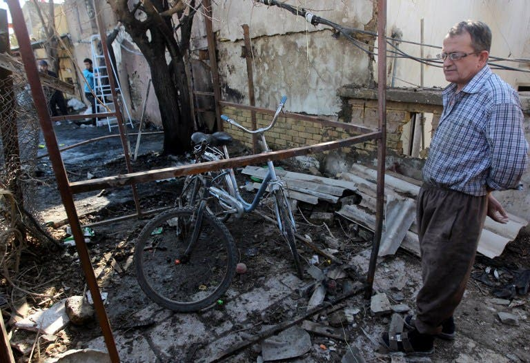 An Iraqi man inspects the site of a car bomb explosion in the Taubchi neighbourhood of the capital Baghdad on January 19, 2014, a day after the attack. [AFP]