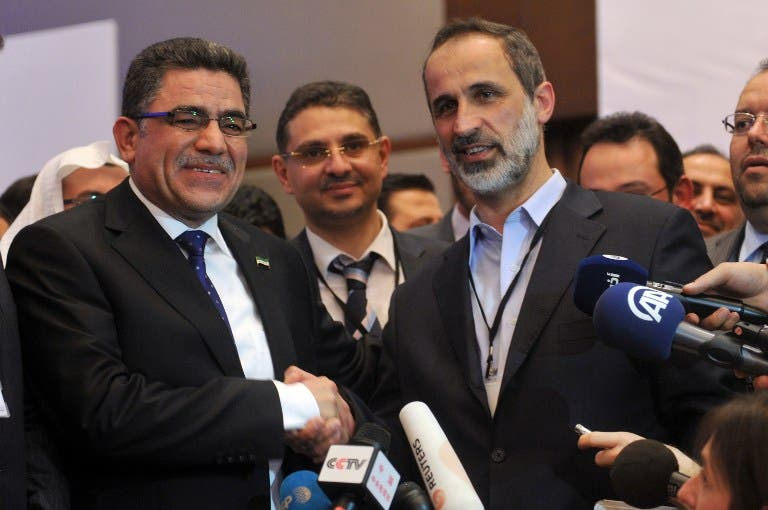 Syria's main opposition National Council chief Moaz al-Khatib (L) congratulates Syrian communications executive, Ghassan Hitto, after the National Council elected him as prime minister. (AFP PHOTO/OZAN KOSE)