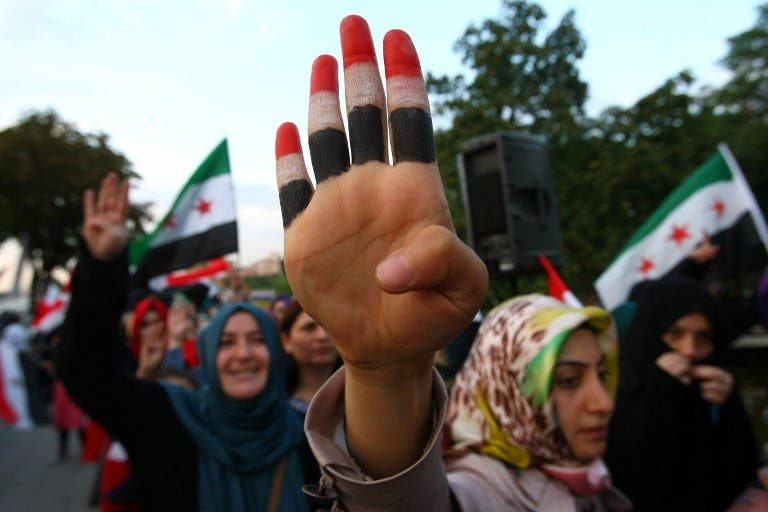 A woman raises her hand painted with the colors of the Egyptian flag among other protesters staging a demonstration in the Turkish capital in Ankara on August 19, 2013. (AFP)