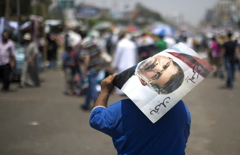 An Egyptian supporter of the Muslim Brotherhood walks holding a poster featuring deposed president Mohamed Morsi during a rally to support him on July 6 (Mahmud Hams / AFP)