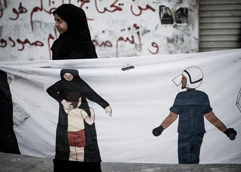 A Bahraini protester holds a banner during an anti-regime rally in solidarity with jailed political activists and against the upcoming Bahrain Formula One Grand Prix. (TOPSHOTS/AFP PHOTO/MOHAMMED AL-SHAIKH)