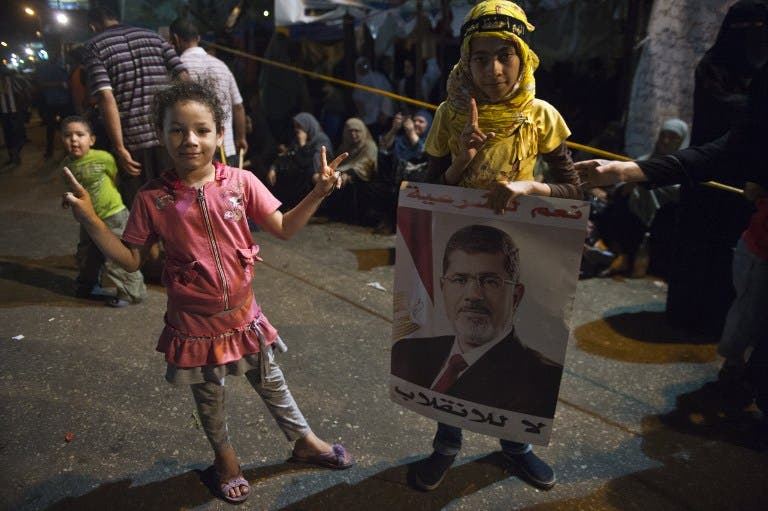 EGYPT, Cairo : Egyptian girls attend with their families supporters of Egypt's deposed president Mohamed Morsi an open sit in outside Rabaa al-Adawiya mosque in Cairo on August 1, 2013. AFP PHOTO / KHALED DESOUKI
