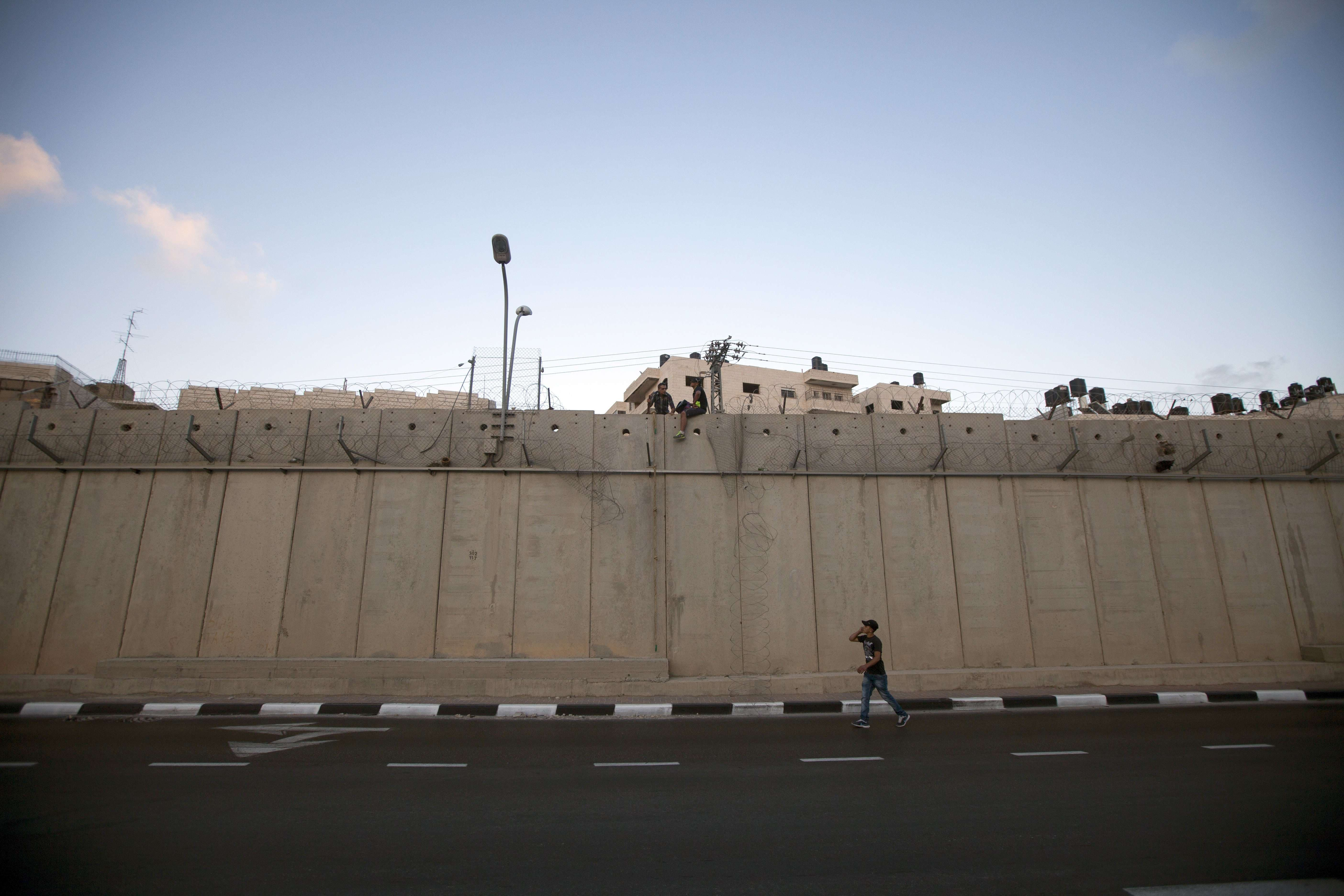 Palestinian men prepare to jump using a rope over a section of Israel's controversial concrete barrier that separates the West Bank from Jerusalem on August 12, 2013, in Beit Hanina, in Israeli annexed east Jerusalem. (AFP)