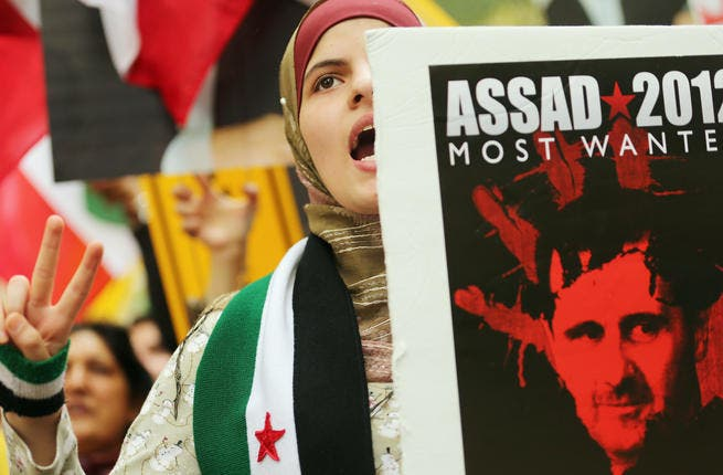Protestors outside the UN General Assembly in New York hold anti-Assad signs