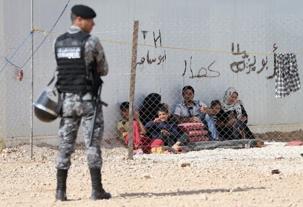 Jordanin Police keep guard as Syrian refugees look on at the King Abdullah Refugee Camp for Syrian refugees 2 kilometers from the Syrian border  (Photo by Chris Jackson/Getty Images)