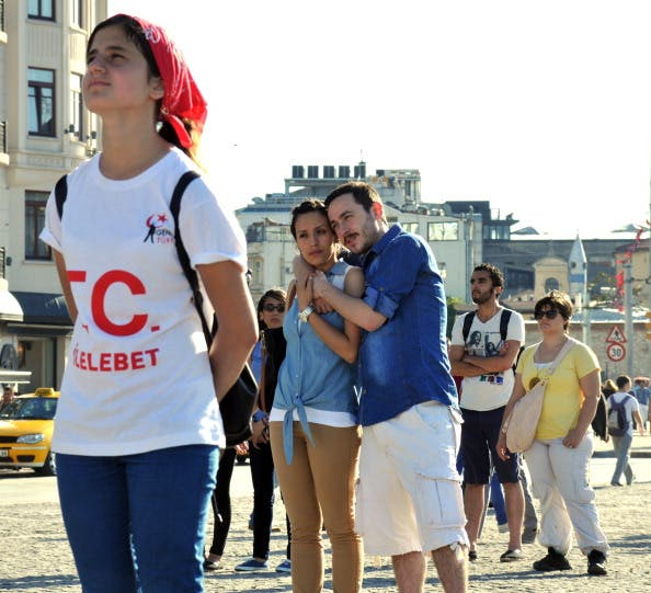 People stand during a silent protest at Taksim Square on June 23 (Getty)