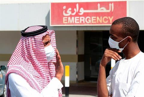 Men wearing surgical masks as a precautionary measure against the novel coronavirus, speak at a hospital in Khobar city in Dammam May 23, 2013.