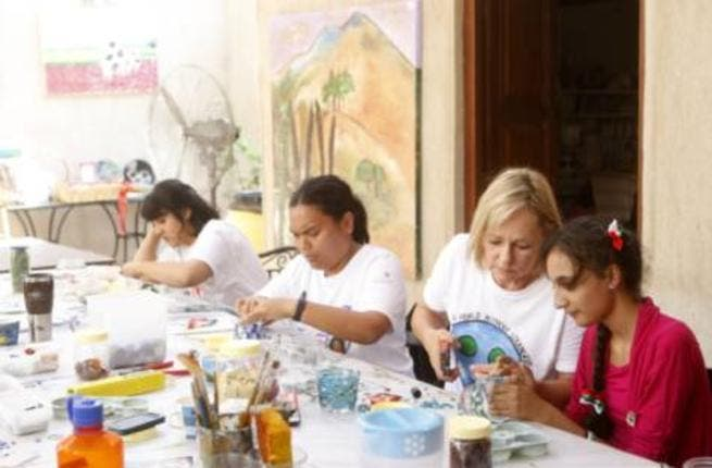 Artists at work: Ange (second from left) and fellow artists engrossed in their creations