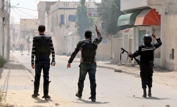 Security forces gesture towards Ansar Al Sharia protestors in the Ettadhamen, Tunisia on Sunday. AFP