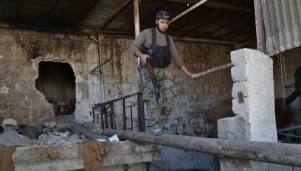 An opposition fighter walks along a log in the northern Syrian city of Aleppo on October 6, 2013. Syria's army took back control of a strategic town in the northern province of Aleppo on October 3, after a weeks-long battle for the city. (AFP)