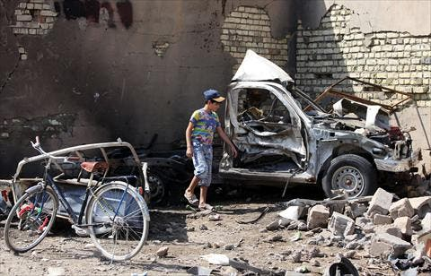 An Iraqi child stands by the wreckage of a burnt car on the site of a car bomb explosion in the city of Suweirah, south of Baghdad, on Sunday. A wave of attacks across Iraq, including more than a dozen car bombs, killed at least 30 people while the head of Baghdad's provincial council escaped assassination. (AFP)