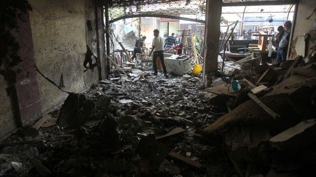 Iraqi men inspect the site of a bomb attack that went off outside a cafe in Baghdad's Bayaa neighborhood. [presstv.ir]