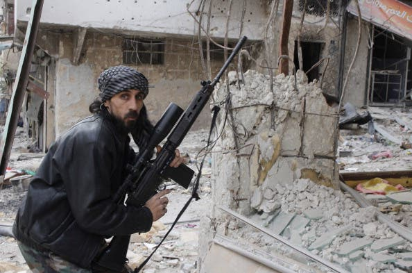 A rebel fighter from the Free Syrian Army holds a position with a Belgium made FAL rifle at a front line in the Salah al-Din neighbourhood of the northern Syrian city of Aleppo, on December 1, 2013. [Getty Images]