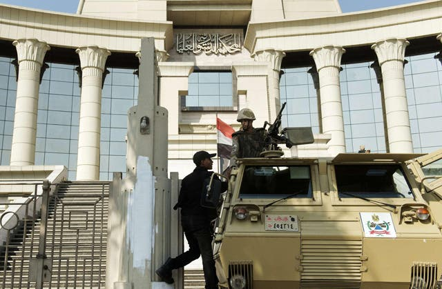 An Egyptian policeman talks to a soldier manning an armoured personnel carrier outside the Egyptian Constitutional Court in Cairo on Monday (AFP photo)