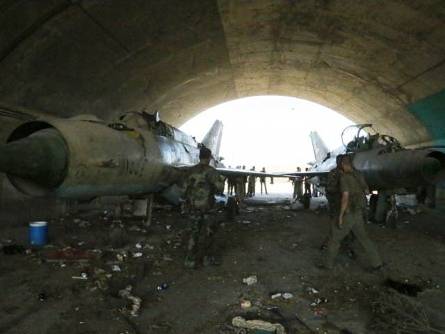 Syrian soldiers look at the damage of a hanger in central Homs. (AFP photo)