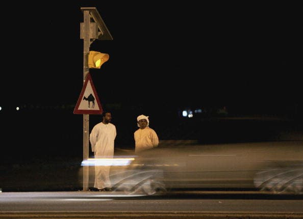 Two men wait to cross the road in a country where red lights are routinely ignored (Getty)