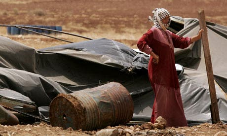 A Palestinian bedouin woman stands next to her destroyed tent in the village of Atouf in the Jordan Valley (AFP/File)