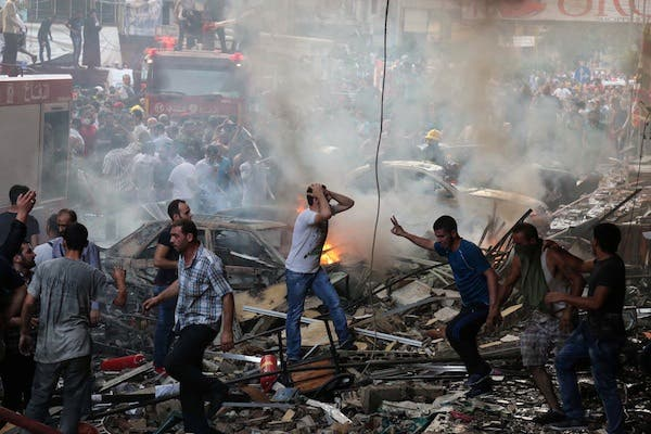 Lebanese civilians and emergency personnel gather at the site of a car bomb between the Bir el-Abed and Roueiss neighbourhoods, in the southern suburb of Beirut on August 15, 2013. (AFP)