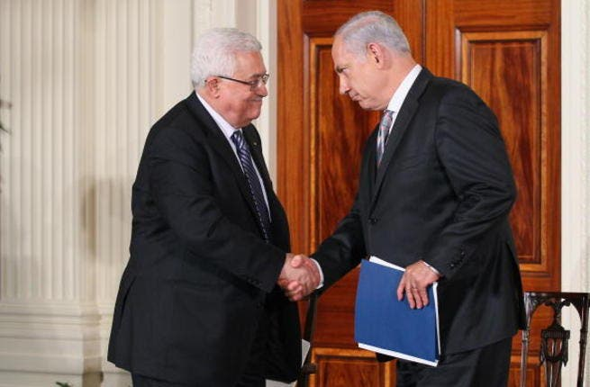 Palestinian Authority President Mahmoud Abbas (L) shakes hands with Israeli Prime Minister Benjamin Netanyahu.