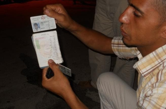 Alaa shows us his tainted ID card