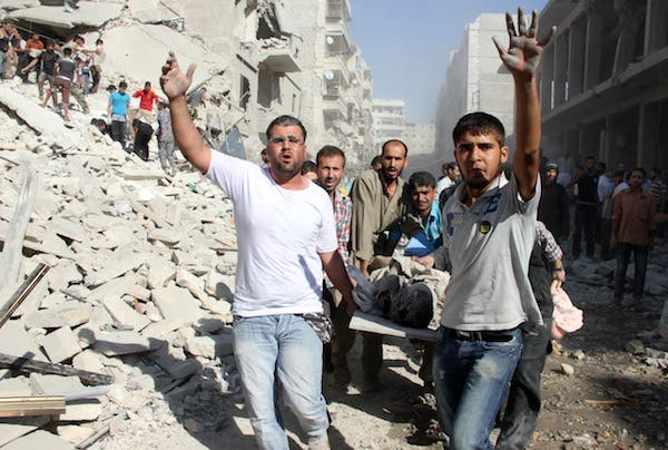 Syrians men evacuat a victim following an air strike by regime forces in the northern city of Aleppo on August 26, 2013. (AFP)