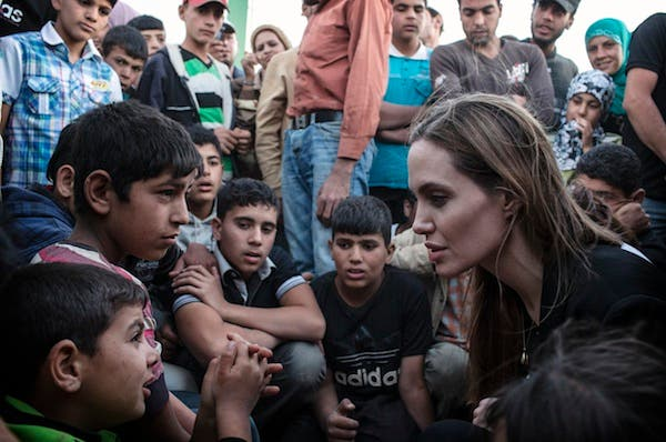 US actress Angelina Jolie speaks with Syrian refugees in a Jordanian military camp based the the Jordan-Syria border on Tuesday. (AFP)