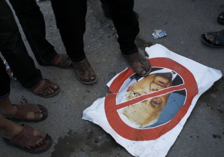 Palestinian supporters of the Islamic Jihad step on a poster bearing a portrait of former Israeli premier Ariel Sharon who died after being in a coma for eight years, aged 85. (AFP)