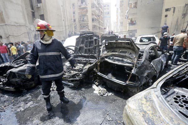 A firefighter stands after extinguishing fire from vehicles at the site of an explosion in Beirut's southern suburb neighbourhood of Bir al-Abed on July 9, 2013. (Source: AFP/STR)