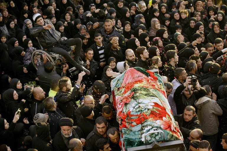 People carry one of the two bodies during the funeral of Malak Zahwa and her step-mother Iman Hijazi, who both died in a car bomb that targeted a Beirut's suburb the day before on January 3, 2014. The death toll of the blast has now risen to six. (AFP)