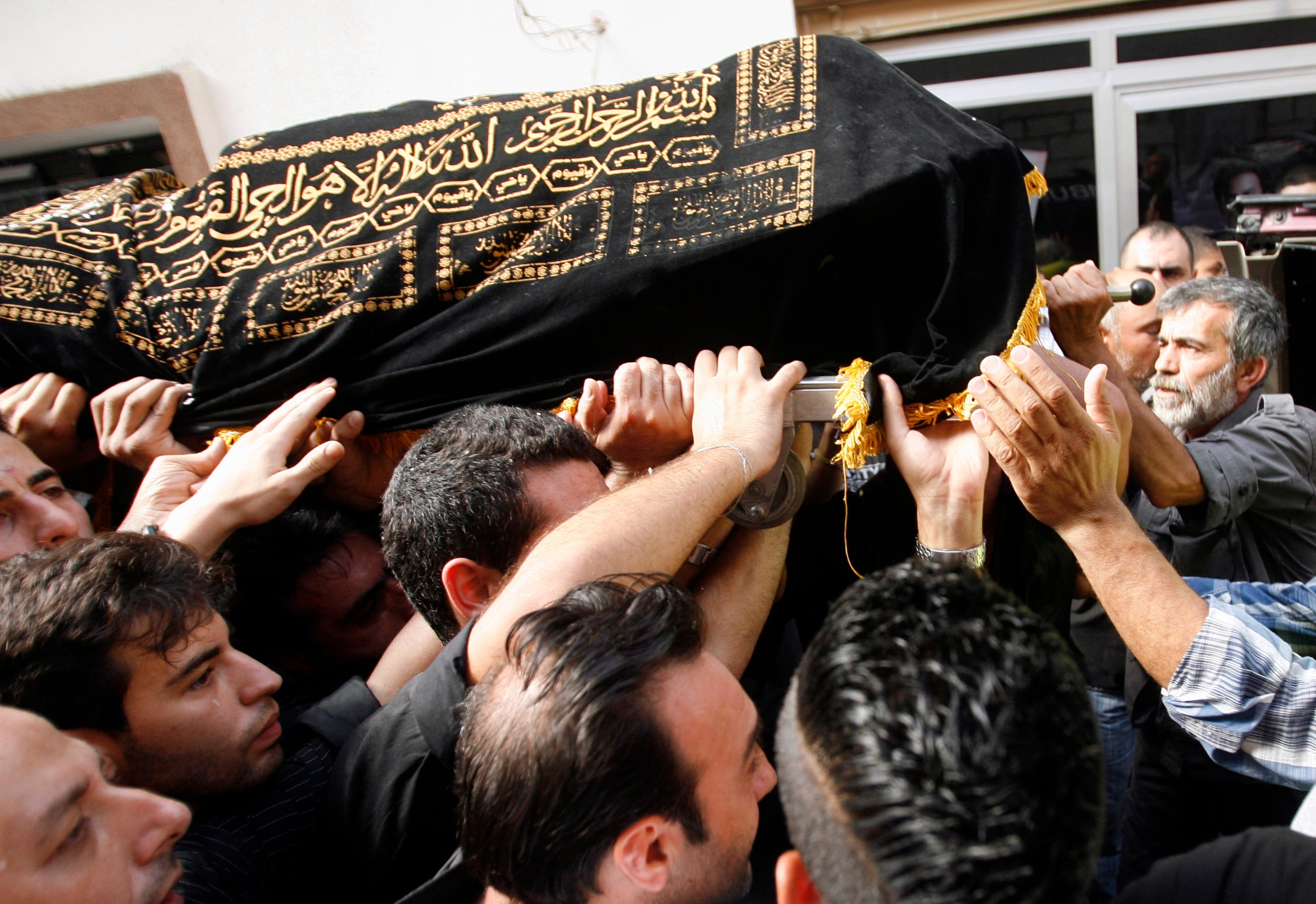 Mourners carry the body of Hassan Ramadan, who was killed in a blast in Beirut earlier in the week, during a funeral in the southern Lebanese village of Jwaya (AFP/MAHMOUD ZAYYAT)