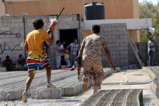 Members of Libyan security forces run away holding weapons during clashes between protesters and troops of the Libyan Shield Forces (LSF), a coalition of militias, in Benghazi. AFP Photo