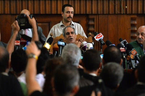 Egyptian judge Mohamed al-Karmouti (C) announces the adjournment of the trial of Muslim Brotherhood Supreme leader Mohamed Badie and 32 other Islamists on August 25, 2013 at a Cairo court. (AFP)