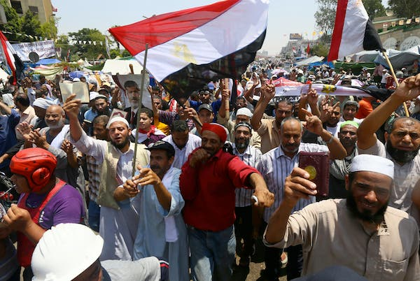Supporters of Egypt's deposed president Mohamed Morsi chant islamic slogans during a rally outside Cairo's Rabaa al-Adawiya mosque on July 13, 2013. (Source: AFP/MARWAN NAAMANI)