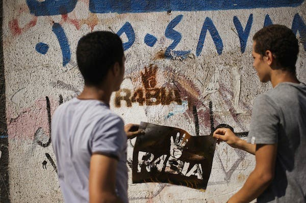 Supporters of the Muslim Brotherhood spray graffiti on the wall reading