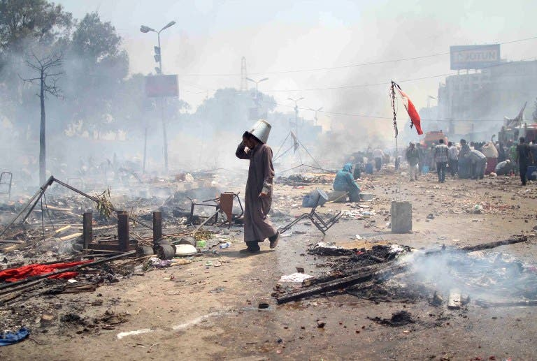 supporter of Egypt's ousted president Mohamed Morsi walks through the debris following clashes with police in Cairo on August 14, 2013. (AFP)