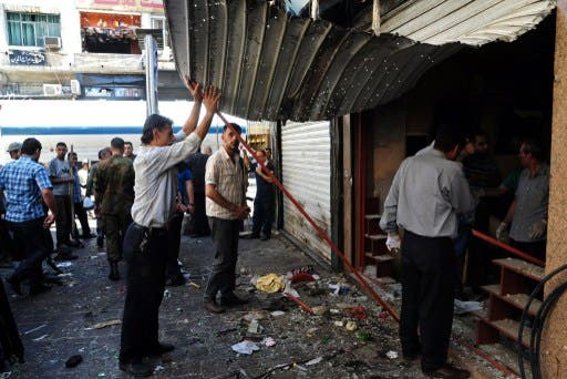 Syrians inspecting the damage in central Damascus following two explosions on Tuesday. AFP photo