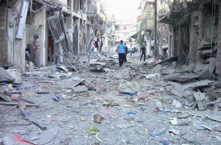 Residents investigate the damage after an alleged shelling attack in Damascus on August 8 2012 (AFP Photo)