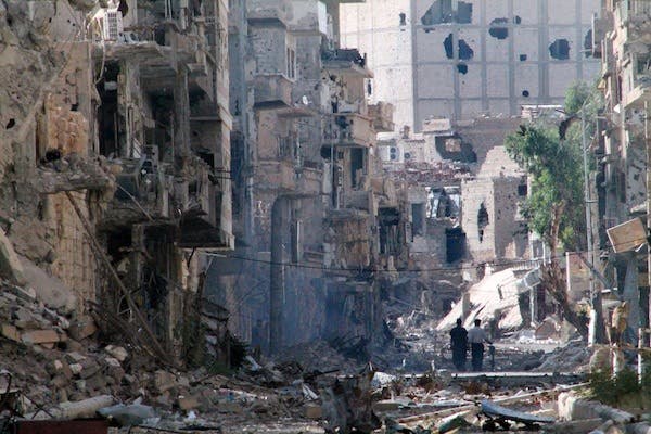 Syrians walk down a destroyed street in the centre of Syria's northeastern city of Deir Ezzor on Thursday. The central city of Homs has been under a fierce aerial bombardment from regime forces, according to the Syrian Observatory for Human Rights. (AFP)