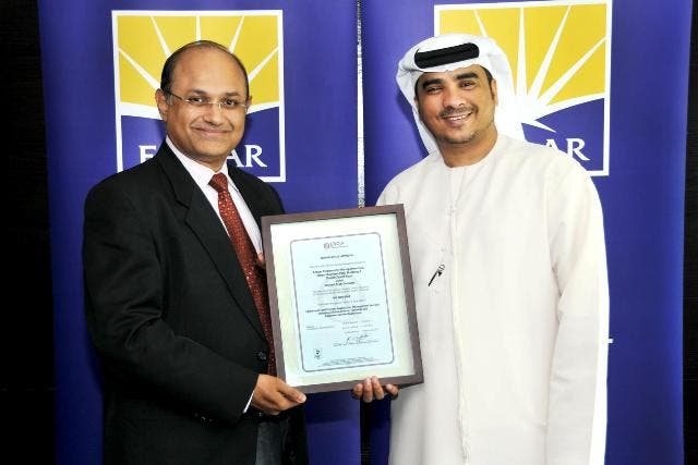 Ahmad Al Falasi, Executive Director and Jeevan J D'Mello, Senior Director of Emaar Community Management receiving the certification from Lloyds Register Quality Assurance
