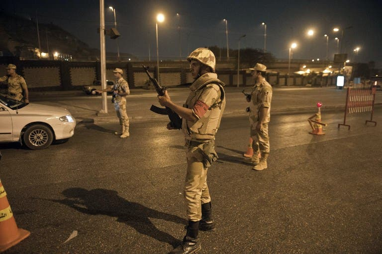 Egyptian troops keep watch at a checkpoint during the curfew hours in Cairo late on August 19, 2013