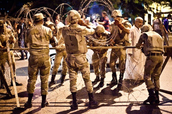 Egyptian army soldiers take out barbed wire that was surrounding the Supreme Constitutional Court in Cairo ahead of planned demonstrations on August 18, 2013. (AFP)