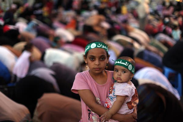An Egyptian girl holds a baby as supporters of the Muslim Brotherhood pray on July 10, 2013. (source: AFP PHOTO / MAHMUD HAMS)